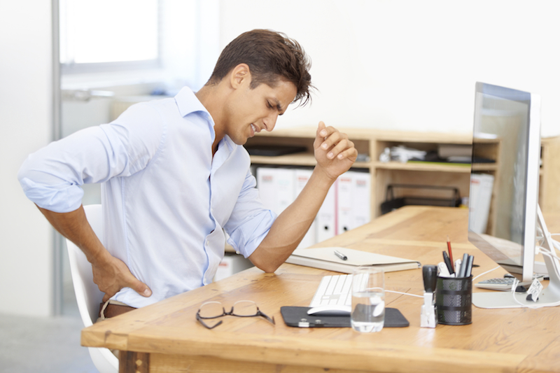 Shot of a businessman rubbing his aching back while sitting at his desk in front of his computer